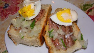 Huevo sobre anchoas del Cantábrico con cebolla y perejil