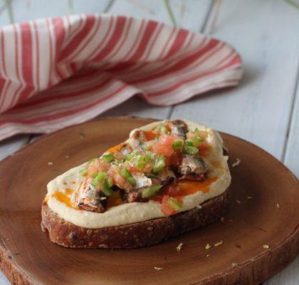 Tostada de hummus con sardinillas