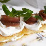 Milhojas de torta de aceite con queso crema, anchoas del Cantábrico y canónigos
