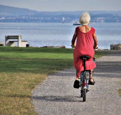 Salud senior. Mujer mayor montando en bici en un parque