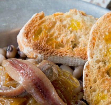 Fréjoles con cebolla caramelizada y anchoas