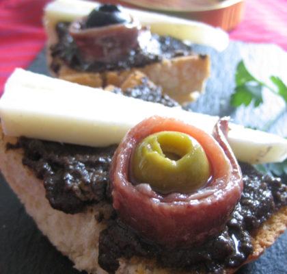Canapé navideño: Tosta de pate de aceitunas negras con queso y anchoas
